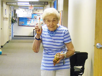 A resident from Trinity Village senior living community participates in Fun Fit Friday with a game of Flick The Fowl.