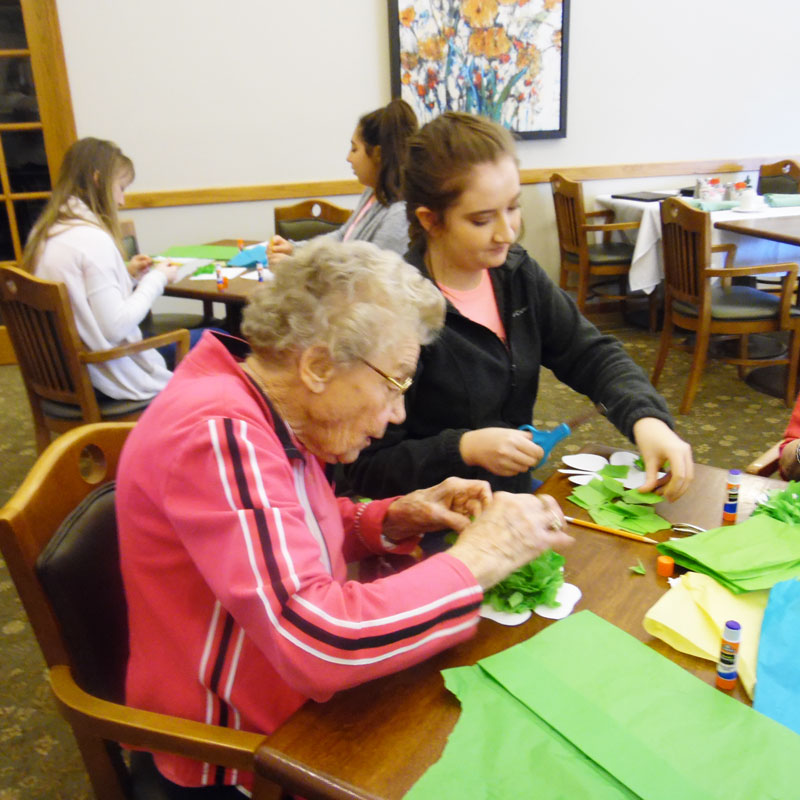 ruby, a trinity village resident, works on her four leaf clover craft with a young lady from the american heart association sweetheart leadership program