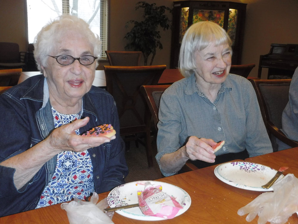 Immanuel Village residents and staff decorate cookies at the community for Valentine's Day