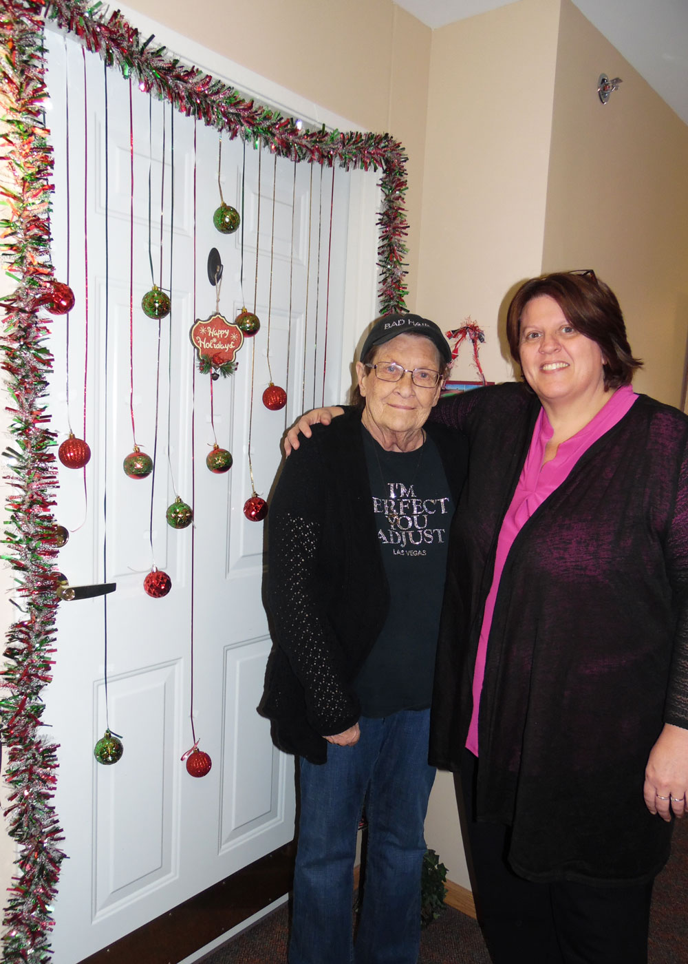 A resident and staff member at Immanuel Courtyard senior living community poses in front of a decorated door during the community's festive door contest
