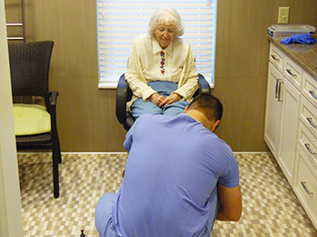 A Pacific Springs Village resident receives a free consultation from a visiting podiatrist