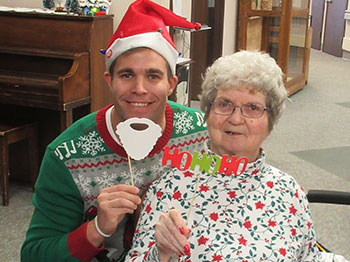 A resident from Immanuel Fontenelle senior living community poses with an employee from Physician's Mutual during a holiday party