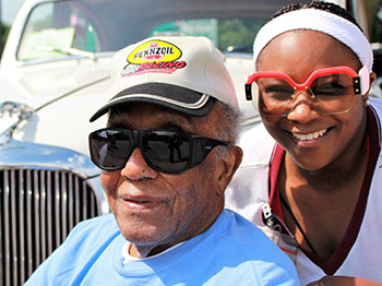 A resident from Immanuel Fontenelle, a senior living community in Omaha, Nebraska, poses alongside his family member and a vintage car during the community's Father's Day car show.