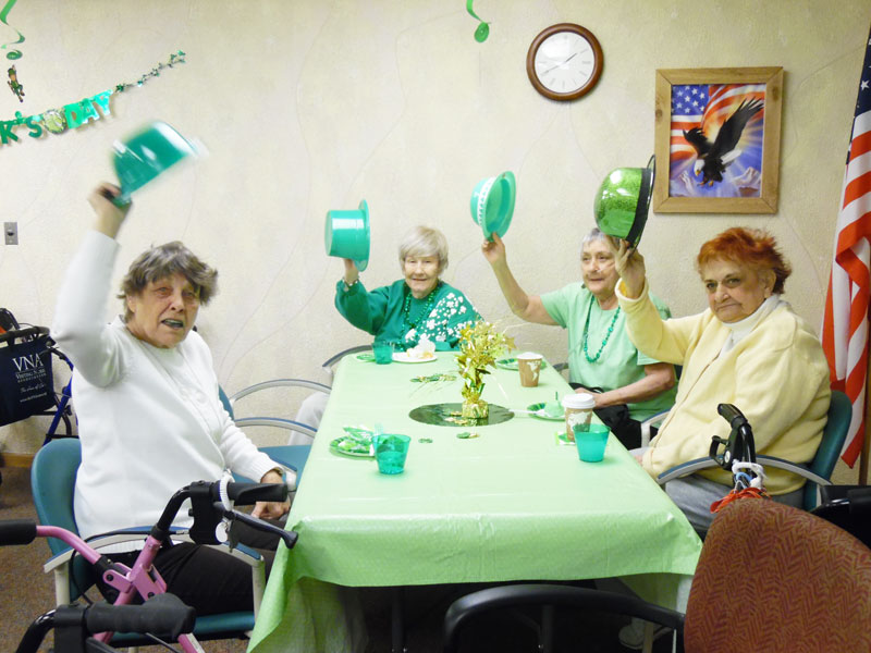 Immanuel Courtyard residents wave their Irish top hats in the air for the camera
